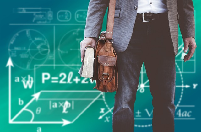 A picture of a man dressed in slacks and a blazer holding a book bag and a book and standing in front of a blackboard covered in math equations.